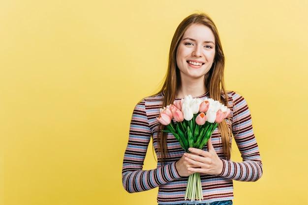 Glückliche frau, die einen blumenstrauß von tulpen hält