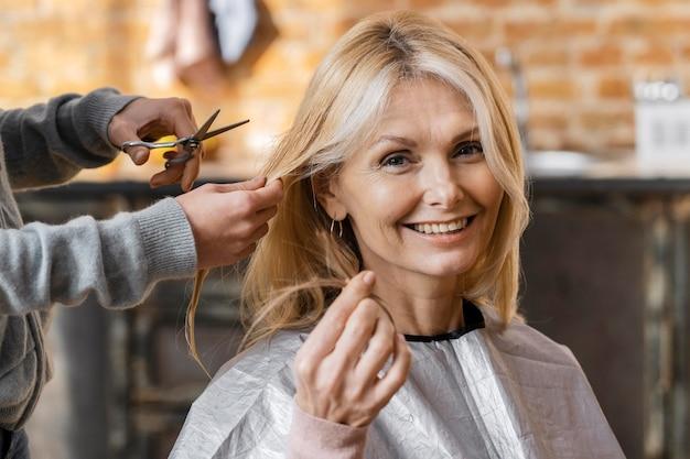 Glückliche frau, die einen haarschnitt zu hause mit friseur bekommt
