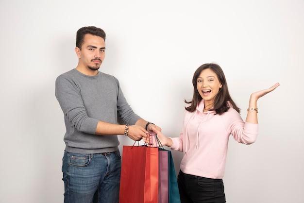 Glückliche frau, die einkaufstaschen zum müden mann gibt, um zu tragen.