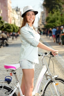 Glückliche frau, die fahrrad auf die straße in der stadt fährt.