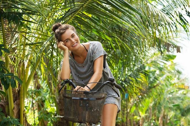 Glückliche frau, die fahrrad im tropischen garten am heißen sommertag reitet