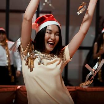 Glückliche frau, die feiert, während sie einen weihnachtsmannhut trägt
