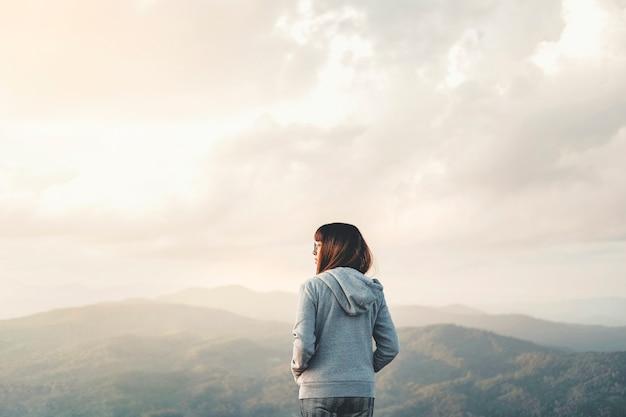 Glückliche frau, die freiheit auf berg mit sonnenuntergangentspannungskonzept genießt