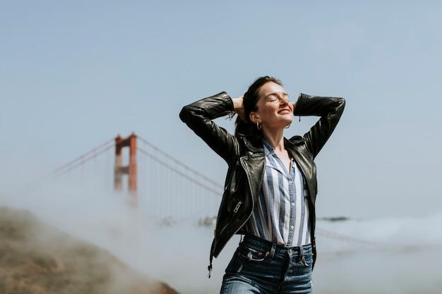 Glückliche frau, die für ein foto bei golden gate bridge, san francisco aufwirft