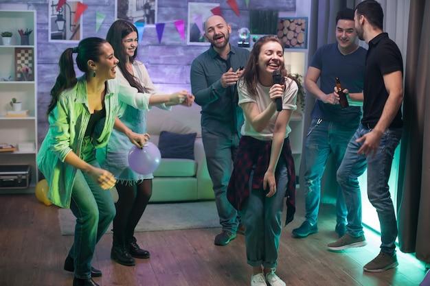 Glückliche frau, die für ihre freunde auf der party singt. karaoke-unterhaltung.