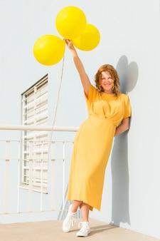 Glückliche frau, die gelbe luftballons hält