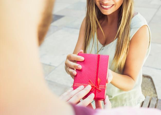 Glückliche frau, die geschenk von ihrem freund empfängt