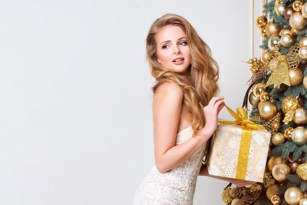 Glückliche frau, die geschenkbox öffnet. luxusblondine mit weihnachtsgeschenk