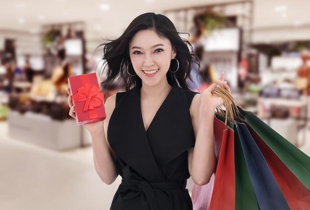 Glückliche frau, die geschenkbox und einkaufstasche am mall hält