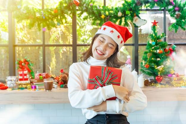 Glückliche frau, die geschenkboxen mit dekoration der frohen weihnachten im fensterhintergrund hält.