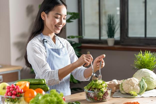 Glückliche frau, die gesunden salat in der küche zubereitet