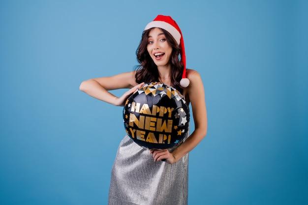 Glückliche frau, die guten rutsch ins neue jahr-ballon hält und den weihnachtshut lokalisiert über blau trägt