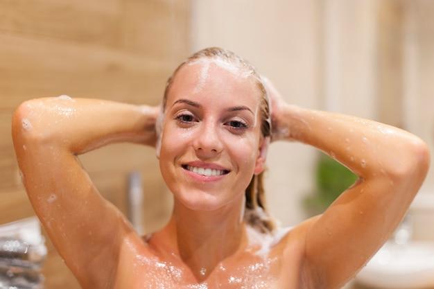 Glückliche frau, die haare unter der dusche wäscht