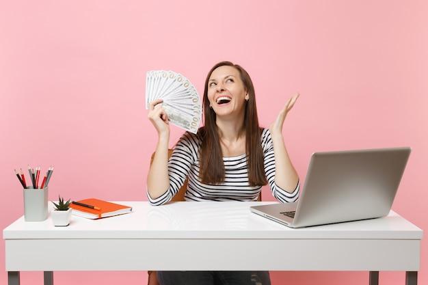 Glückliche frau, die hände ausbreitet, die bündel viele dollar halten, bargeld, das am projekt im büro am weißen schreibtisch mit pc-laptop arbeitet