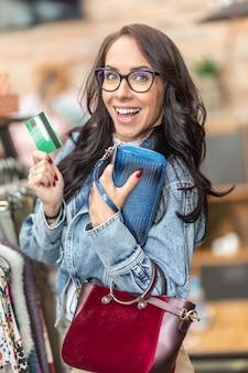 Glückliche frau, die handtaschen im modegeschäft kauft und eine grüne zahlungskarte in der hand hält.