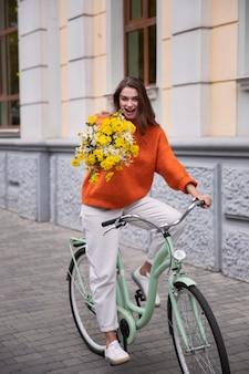 Glückliche frau, die ihr fahrrad draußen mit blumen reitet