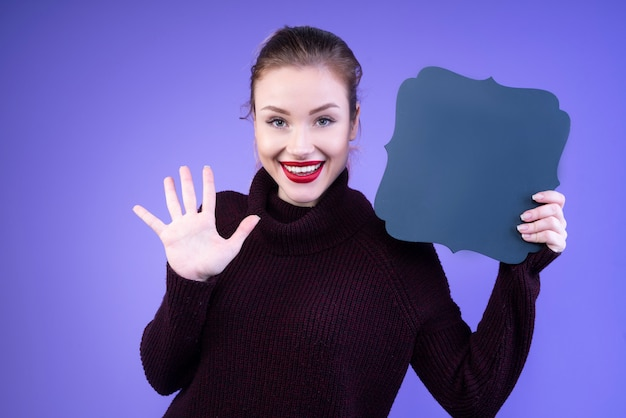 Glückliche frau, die ihre fünf finger und einen dunkelblauen karton zeigt