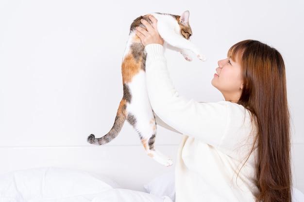 Glückliche frau, die ihre reizende flauschige katze hält.