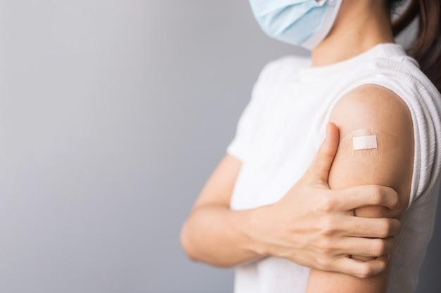 Glückliche frau, die ihren arm mit verband zeigt, nachdem sie den impfstoff erhalten hat. impfung, impfung, impfung und coronavirus (covid-19) pandemie