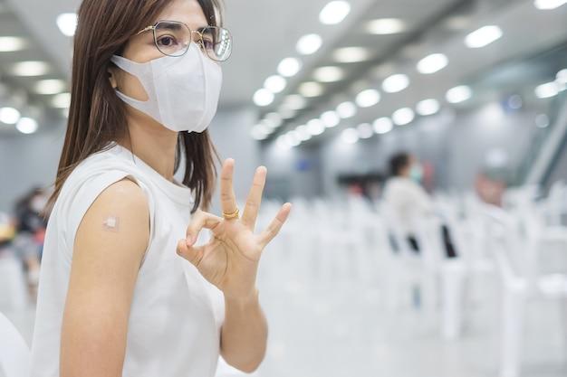 Glückliche frau, die ihren arm mit verband zeigt und nach erhalt des impfstoffs ein gutes handzeichen gibt. impfung, impfung, impfung und coronavirus (covid-19) pandemie