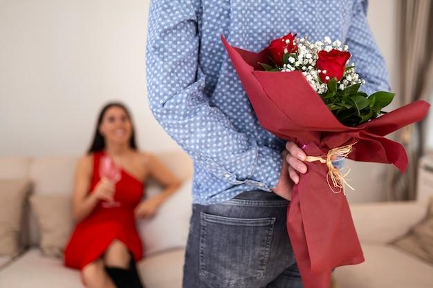 Glückliche frau, die ihren freund betrachtet, der rosenstrauß hinter seinem rücken hält.