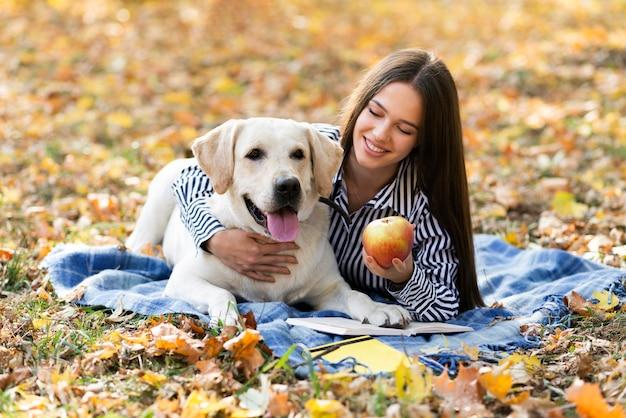 Glückliche frau, die ihren hund im park hält