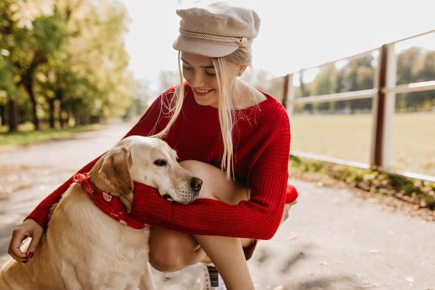 Glückliche frau, die ihren hund zärtlich im herbstpark hält. schönes blondes mädchen, das gute zeit mit haustier im freien hat.