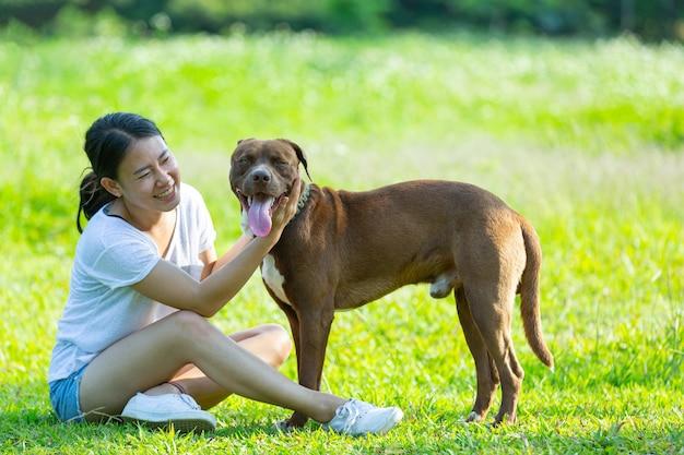 Glückliche frau, die ihren lieblingshund im park genießt.