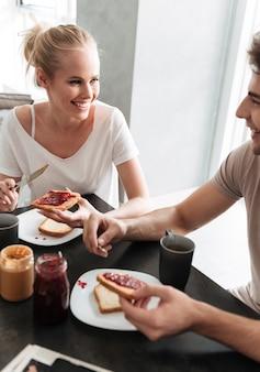 Glückliche frau, die ihren mann betrachtet, während sie frühstück essen
