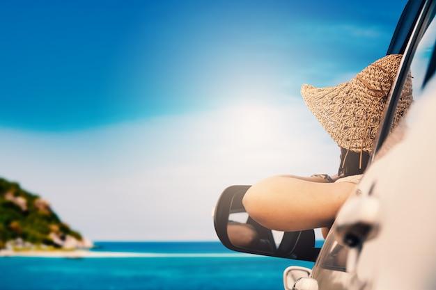 Glückliche frau, die im auto und in der reisenden sommersaison auf dem meer stillsteht und spezieller tag zu den ferien sitzt.