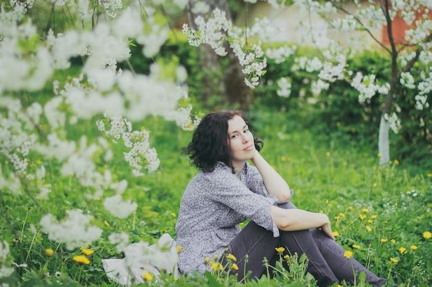 Glückliche frau, die im frühlingskirschgarten sitzt sitting