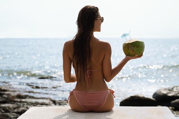 Glückliche frau, die im schwimmbad entspannt und kokoswasser trinkt
