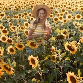 Glückliche frau, die im sonnenblumenfeld aufwirft