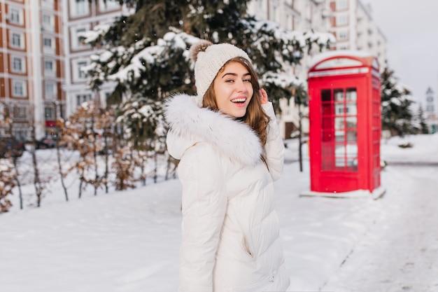 Glückliche frau, die im sonnigen wintermorgen mit lächeln herumläuft. faszinierende frau in strickmütze, die über schulter schaut und auf verschneiter straße mit roter telefonzelle aufwirft