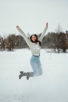 Glückliche frau, die im winter draußen springt