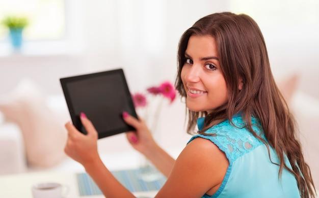 Glückliche frau, die in der hand digitales tablett hält