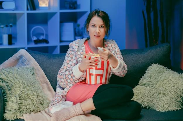 Glückliche frau, die in der sofa-couch des wohnzimmers sitzt und lustiges interessantes programm beobachtet und zeigt, wie man nachts popcorn isst.