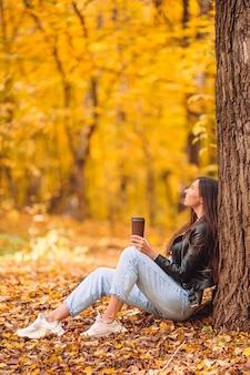 Glückliche frau, die kaffee im herbstpark unter herbstlaub trinkt. goldener herbstpark