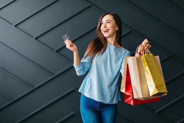 Glückliche frau, die kreditkarte und taschen mit einkäufen hält