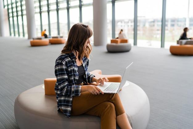 Glückliche frau, die laptop beim sitzen am flughafenlounge verwendet.
