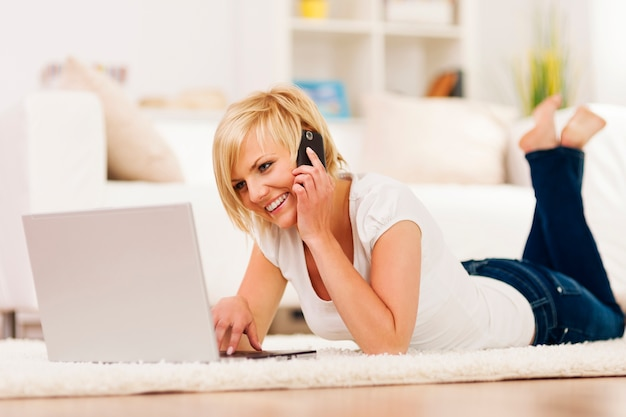 Glückliche frau, die laptop benutzt und auf handy spricht