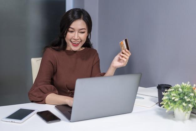 Glückliche frau, die laptop-computer für das on-line-einkaufen mit kreditkarte verwendet