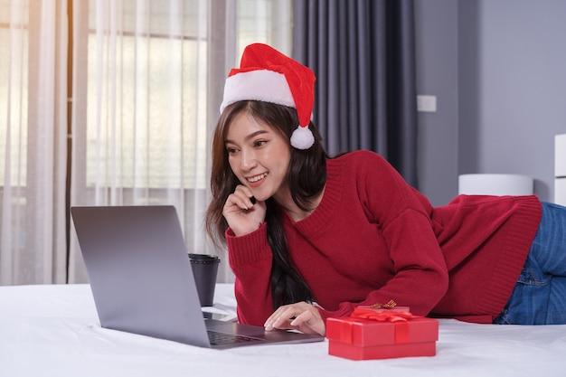 Glückliche frau, die laptop-computer mit weihnachtsgeschenk auf bett verwendet