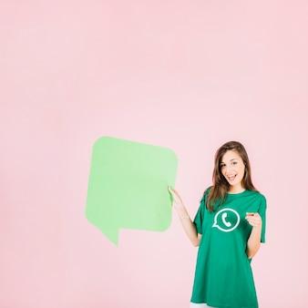 Glückliche frau, die leere grüne spracheblase hält