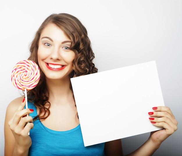Glückliche frau, die leere karte und lutscher hält. über weißem hintergrund lächelndes weibliches porträt.