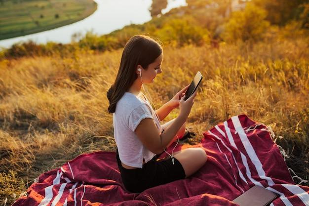 Glückliche frau, die lieblingslieder hört, während sie auf plaid auf dem hügel sitzt.