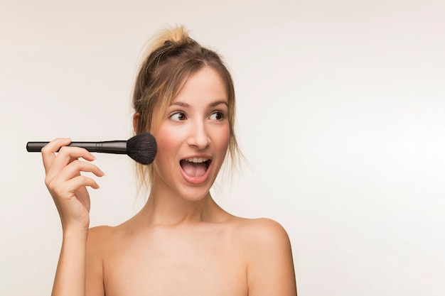 Glückliche frau, die make-upbürste hält