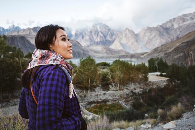 Glückliche frau, die mit blick auf die himalaja-berge steht