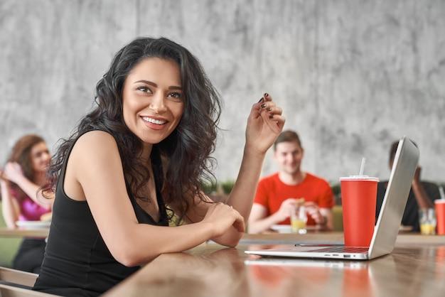 Glückliche frau, die mit computer im café arbeitet und zu mittag isst. junges schönes mädchen, das in internet surft