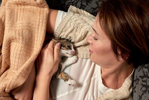 Glückliche frau, die mit der katze im schlafzimmer spielt